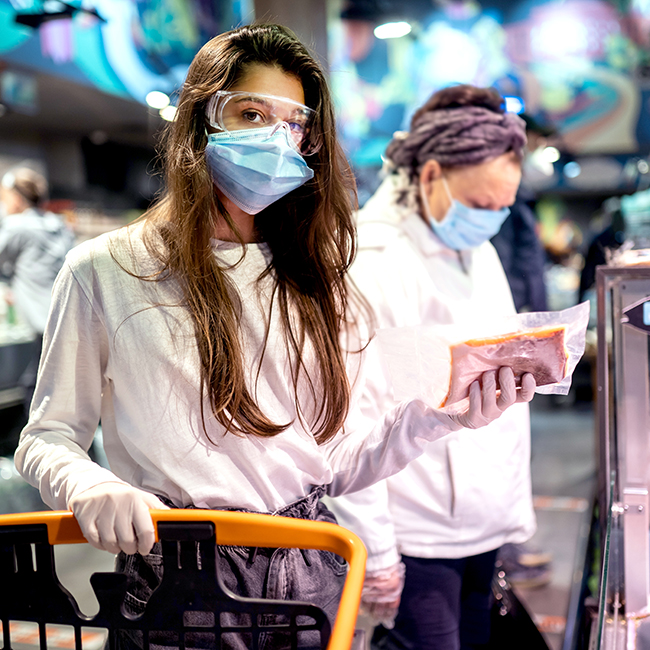 Woman with the surgical mask and the gloves is shopping in the supermarket