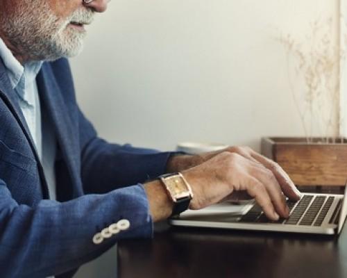 Elderly man is using computer laptop